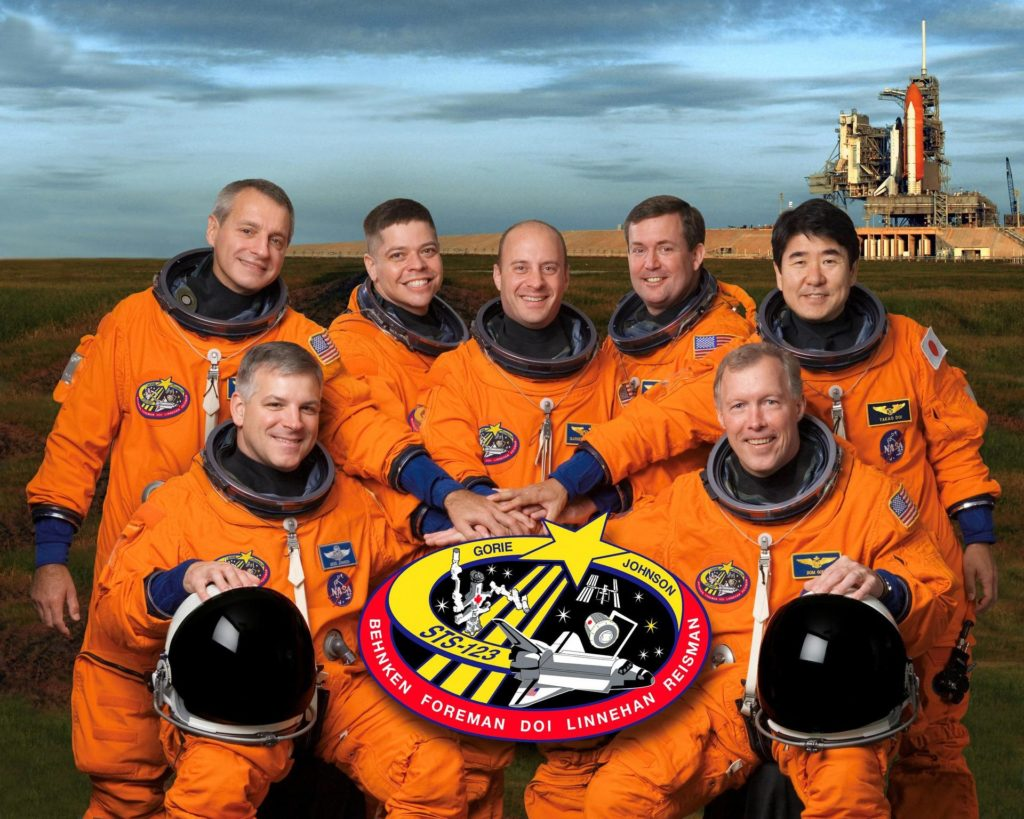 JOHNSON SPACE CENTER, HOUSTON -- STS123-S-002-- These seven astronauts take a break from training to pose for the STS-123 crew portrait.  From the right (front row) are astronauts Dominic L. Gorie, commander, and Gregory H. Johnson, pilot.  From the left (back row) are astronauts Richard M. Linnehan, Robert L. Benken, Garrett E. Reisman, Michael J. Foreman and Japan Aerospace Exploration Agency's (JAXA) Takao Doi, all mission specialists.  Reisman is scheduled to join Expedition 16 as flight engineer after launching to the International Space Station on mission STS-123.  The crewmembers are attired in training versions of their shuttle launch and entry suits. KSC-08pd0364