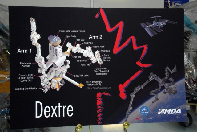 KENNEDY SPACE CENTER, FLA. --  A poster in the Space Station Processing Facility, or SSPF, at NASA's Kennedy Space Center illustrates the assembled Dextre, the third and final component of the mobile servicing system on the International Space Station.  The Special Purpose Dexterous Manipulator will work with the mobile base and Canadarm2 on the station to perform critical construction and maintenance tasks. The poster sits in front of the draped sections in the SSPF.  Dextre is part of the payload scheduled on mission STS-123, targeted to launch Feb. 14, 2008. Photo credit: NASA/George Shelton KSC-07pd2366