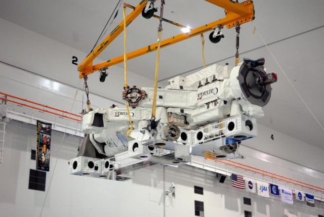 KENNEDY SPACE CENTER, FLA. -- In the Space Station Processing Facility at NASA's Kennedy Space Center, a crane lifts the Special Purpose Dexterous Manipulator, known as Dextre, to position it onto a pallet.  Processing of the payload is under way for its mission to the International Space Station. Dextre will work with the mobile base and Canadarm2 on the station to perform critical construction and maintenance tasks. Dextre is part of the payload scheduled on mission STS-123, targeted to launch Feb. 14, 2008.  Photo credit: NASA/Kim Shiflett KSC-07pd2562