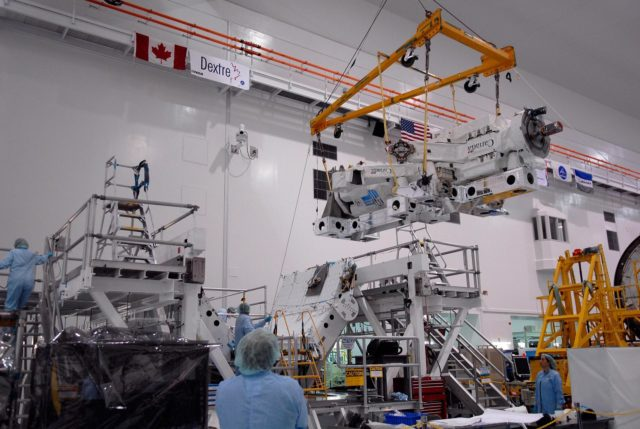 KENNEDY SPACE CENTER, FLA. -- In the Space Station Processing Facility at NASA's Kennedy Space Center, technicians monitor the Special Purpose Dexterous Manipulator, known as Dextre, as a crane moves it near its destination onto a pallet.  Processing of the payload is under way for its mission to the International Space Station. Dextre will work with the mobile base and Canadarm2 on the station to perform critical construction and maintenance tasks. Dextre is part of the payload scheduled on mission STS-123, targeted to launch Feb. 14, 2008.  Photo credit: NASA/Kim Shiflett KSC-07pd2565