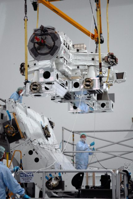 KENNEDY SPACE CENTER, FLA. -- In the Space Station Processing Facility at NASA's Kennedy Space Center, technicians guide the Special Purpose Dexterous Manipulator, known as Dextre, as a crane lowers it toward a pallet.  Processing of the payload is under way for its mission to the International Space Station. Dextre will work with the mobile base and Canadarm2 on the station to perform critical construction and maintenance tasks. Dextre is part of the payload scheduled on mission STS-123, targeted to launch Feb. 14, 2008.  Photo credit: NASA/Kim Shiflett KSC-07pd2566