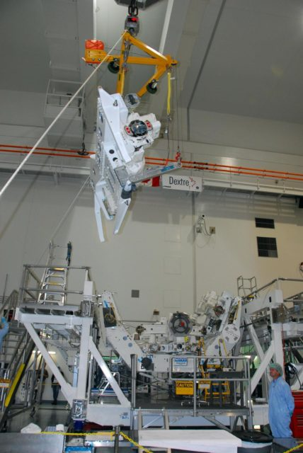 KENNEDY SPACE CENTER, FLA. -- In the Space Station Processing Facility at NASA's Kennedy Space Center, the starboard arm of the Special Purpose Dexterous Manipulator, known as Dextre, is moved toward the base, in the background.  The arm will be installed on the base.  Dextre is a sophisticated dual-armed robot, which is part of Canada's contribution to the International Space Station (ISS). Along with Canadarm2, whose technical name is the Space Station Remote Manipulator System, and a moveable work platform called the Mobile Base System, these three elements form a robotic system called the Mobile Servicing System, or MSS. The three components have been designed to work together or independently. Dextre is part of the payload scheduled on mission STS-123, targeted to launch Feb. 14.  Photo credit: NASA/George Shelton KSC-07pd2867