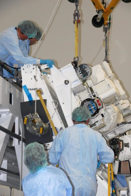 KENNEDY SPACE CENTER, FLA. -- In the Space Station Processing Facility at NASA's Kennedy Space Center, technicians help guide the starboard arm of the Special Purpose Dexterous Manipulator, known as Dextre, into place for installation on the base.   Dextre is a sophisticated dual-armed robot, which is part of Canada's contribution to the International Space Station (ISS). Along with Canadarm2, whose technical name is the Space Station Remote Manipulator System, and a moveable work platform called the Mobile Base System, these three elements form a robotic system called the Mobile Servicing System, or MSS. The three components have been designed to work together or independently. Dextre is part of the payload scheduled on mission STS-123, targeted to launch Feb. 14.  Photo credit: NASA/George Shelton KSC-07pd2870