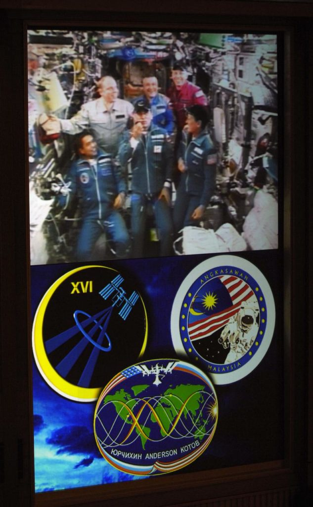 """Live video from the International Space Station is shown on the screen in the Russian Mission Control Center in Korolev, outside Moscow, October 12, 2007. Expedition 16 Commander Peggy Whitson (bottom right), Soyuz Commander and Flight Engineer Yuri Malenchenko (bottom center) and Malaysian Spaceflight Participant Sheikh Muszaphar Shukor (bottom left) docked their Soyuz TMA-11 spacecraft to the station at 10:50 a.m. EDT. Oct. 12, 2007. (top left to right) Expedition 15 Commander Fyodor Yurchikhin and Flight Engineers Oleg Kotov and Clay Anderson welcomed the new crew aboard the station when the hatches were opened at 12:22p.m. EDT. Both crews will work together for about nine days before Yurchikhin, Kotov and Shukor depart in their Soyuz TMA-10 spacecraft. Photo Credit: """"NASA/Bill Ingalls"""" 07pd2861"""
