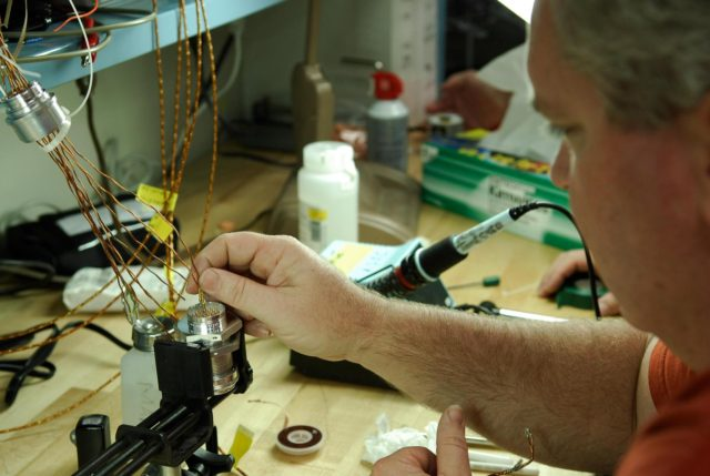 KENNEDY SPACE CENTER, FLA. -- At a lab at NASA's Kennedy Space Center, Bob Arp, an aerospace technician with the United Launch Alliance, inserts a wire from an electrical harness onto the pin of a replacement feed-through connector during preparations to solder the pins to the socket of the connector.  The connector will be installed in the external fuel tank for space shuttle Atlantis' STS-122 mission. The technician performed this exacting task on the Centaur upper stage for Atlas and Titan launches in 1994 and was specifically chosen for the task.   Soldering the connector pins and sockets together addresses the most likely cause of a problem in the engine cutoff sensor system, or ECO system.  Some of the tank's ECO sensors failed during propellant tanking for launch attempts on Dec. 6 and Dec. 9.  Results of a tanking test on Dec. 18 pointed to an open circuit in the feed-through connector wiring, which is located at the base of the tank. The feed-through connector passes the wires from the inside of the tank to the outside.  After the soldering is completed and the connector is reinstalled, shuttle program managers will decide on how to proceed.  The launch date for mission STS-122 is under review.  Photo credit: NASA/Kim Shiflett KSC-08pd0005