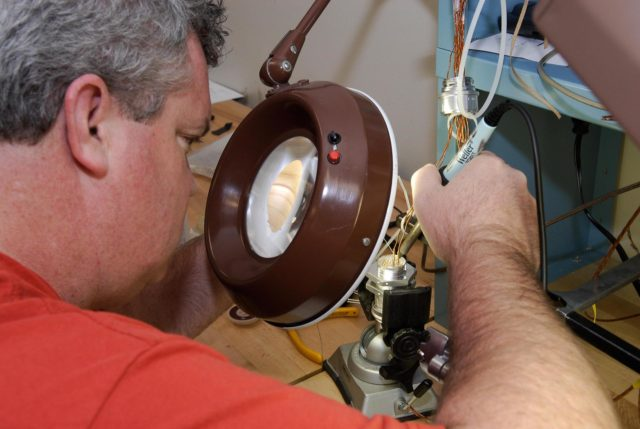KENNEDY SPACE CENTER, FLA. -- At a lab at NASA's Kennedy Space Center, Bob Arp, an aerospace technician with the United Launch Alliance, solders a pin to the socket of the replacement feed-through connector that will be installed in the external fuel tank for space shuttle Atlantis' STS-122 mission. The technician performed this exacting task on the Centaur upper stage for Atlas and Titan launches in 1994 and was specifically chosen for the task.   Soldering the connector pins and sockets together addresses the most likely cause of a problem in the engine cutoff sensor system, or ECO system.  Some of the tank's ECO sensors failed during propellant tanking for launch attempts on Dec. 6 and Dec. 9.  Results of a tanking test on Dec. 18 pointed to an open circuit in the feed-through connector wiring, which is located at the base of the tank. The feed-through connector passes the wires from the inside of the tank to the outside.  After the soldering is completed and the connector is reinstalled, shuttle program managers will decide on how to proceed.  The launch date for mission STS-122 is under review.  Photo credit: NASA/Kim Shiflett KSC-08pd0006