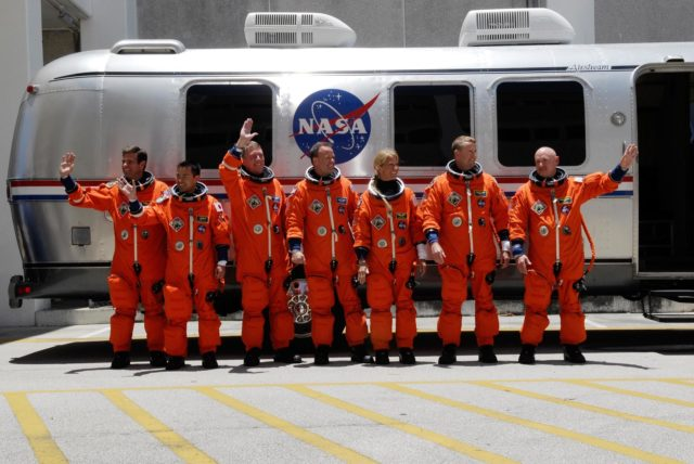 CAPE CANAVERAL, Fla. --  Crew members for space shuttle Discovery's STS-124 mission pause by the Astrovan to wave to spectators before their ride to Launch Pad 39A at NASA's Kennedy Space Center.  From left are Mission Specialists Gregory Chamitoff, Akihiko Hoshide, Mike Fossum, Ron Garan and Karen Nyberg, Pilot Ken Ham and Commander Mark Kelly.  Hoshide represents the Japan Aerospace Exploration Agency.  Chamitoff will join the Expedition 17 crew on the International Space Station as a flight engineer, taking the place of astronaut Garrett Reisman, who will return to Earth on Discovery. The STS-124 mission is the second of three flights launching components to complete the Japan Aerospace Exploration Agency's Kibo laboratory.  The shuttle crew will install Kibo's large Japanese Pressurized Module and its remote manipulator system, or RMS.  The 14-day flight includes three spacewalks.  Launch is scheduled for 5:02 p.m. May 31. Photo credit: NASA/Kim Shiflett KSC-08pd1522