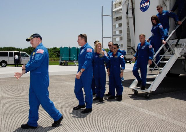 CAPE CANAVERAL, Fla.  –  After their successful STS-124 mission and landing on Runway 15 at NASA's Kennedy Space Center, crew members exit the crew transport vehicle.  Leading the way is Commander Mark Kelly, followed by (from left) Mission Specialists Mike Fossum, Karen Nyberg, Akihiko Hoshide and Ron Garan.  Behind them is Stephen Lindsay, chief of the Astronaut Corps, and astronaut Janet Kavandi.  Space shuttle Discovery's main landing gear touched down at 11:15:19 a.m. EDT on Runway 15. The nose landing gear touched down at 11:15:30 a.m. and wheel stop was at 11:16:19 a.m. The mission completed 5.7 million miles. The STS-124 mission delivered the Japan Aerospace Exploration Agency's large Japanese Pressurized Module and its remote manipulator system to the space station.   Photo credit: NASA/Kim Shiflett KSC-08pd1714