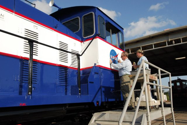 CAPE CANAVERAL, Fla. –   At NASA's Kennedy Space Center in Florida, Phil Moore (left) and Ron Burrill place a new NASA insignia on the side of NASA Railroad locomotive 3.  The Railroad Operation and Maintenance Team at Kennedy completed the refurbishment of locomotive 3 in October. The 15-month process, including a new paint scheme, dealt with extensive corrosion to the locomotive because of Kennedy's proximity to the Atlantic Ocean.  Locomotives 1 and 2 also will be refurbished eventually.  The NASA Railroad locomotives are SW-1500 switch engines built by Electro Motive Diesel (EMD).  Photo credit:  NASA/Amanda Diller KSC-08pd3581