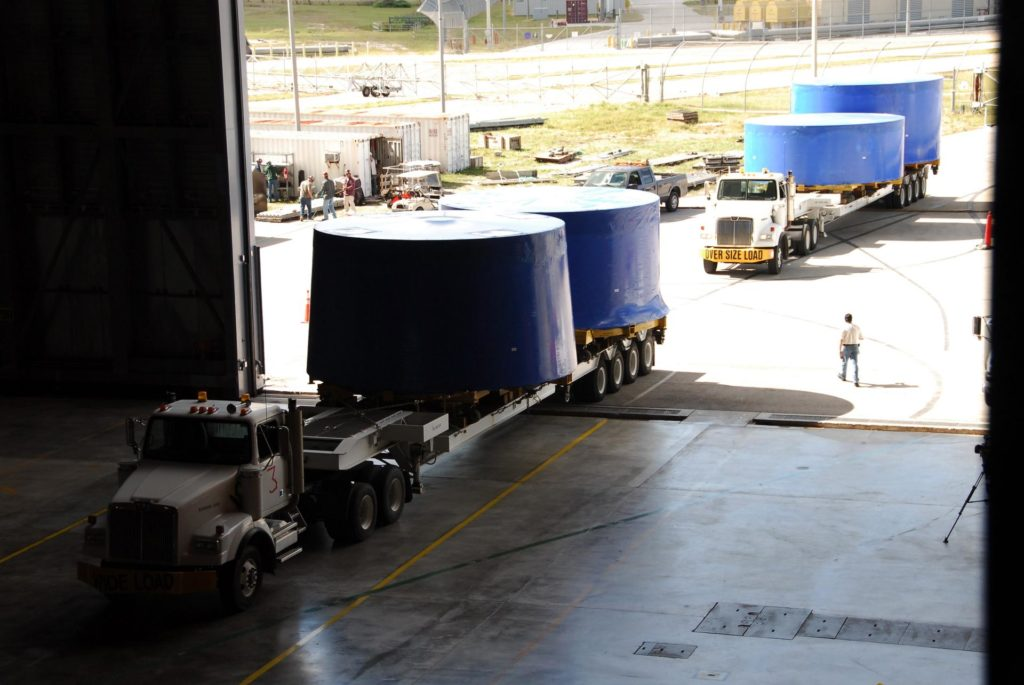 CAPE CANAVERAL, Fla. –   Trucks pull into the Vehicle Assembly Building's high bay 4 at NASA's Kennedy Space Center in Florida.  They carry Ares I-X upper stage simulator segments that arrived Nov. 4 at Port Canaveral, Fla., aboard the Delta Mariner. The upper stage simulators will be used in the test flight identified as Ares I-X in 2009.  The Ares I-X test flight will provide NASA an early opportunity to test and prove hardware, facilities and ground operations associated with the Ares I crew launch vehicle. It also will allow NASA to gather critical data during ascent of the integrated Orion crew exploration vehicle and the Ares I rocket. The data will ensure the entire vehicle system is safe and fully operational before astronauts begin traveling to orbit.  The simulator segments will simulate the mass and the outer mold line and will be more than 100 feet of the total vehicle height of 327 feet.  The simulator comprises 11 segments that are approximately 18 feet in diameter.  Most of the segments will be approximately 10 feet high, ranging in weight from 18,000 to 60,000 pounds, for a total of approximately 450,000 pounds.  Photo credit: NASA/Cory Huston KSC-08pd3525
