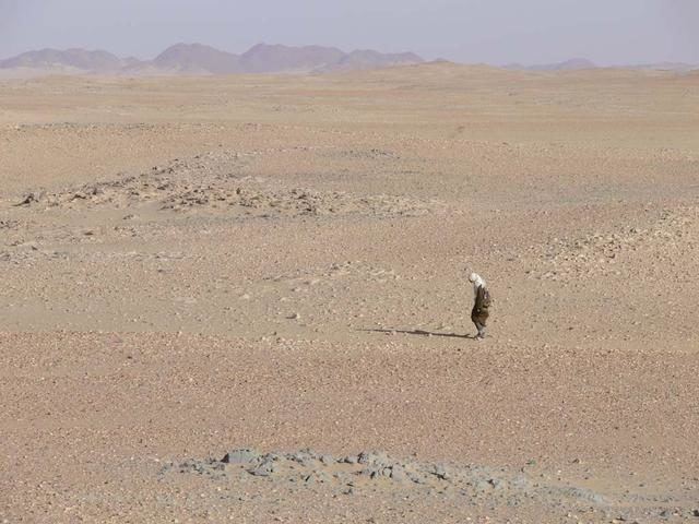An SUV-sized Asteroid 2008TC# Impacts on October 7, 2008 in the Nubian Desert, Northern Sudan: Dr. Peter Jenniskens, NASA/SETI joined Muawia Shaddas of the University of Khartoum in leading an expedition on a search for samples.  searching in the desert  Photo Credit: NASA/SETI/P. Jenniskens ARC-2009-ACD09-0108-045