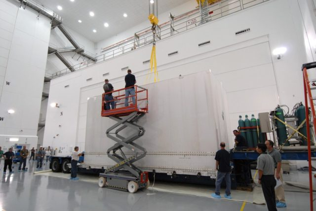 CAPE CANAVERAL, Fla. – At Astrotech Space Operations in Titusville, Fla., workers secure an overhead crane to the shipping container that holds NASA's Solar Dynamics Observatory, or SDO.  SDO is the first space weather research network mission in NASA's Living With a Star Program.  The spacecraft's long-term measurements will give solar scientists in-depth information about changes in the sun's magnetic field and insight into how they affect Earth.  In preparation for its anticipated November launch, engineers will perform a battery of comprehensive tests to ensure SDO can withstand the stresses and vibrations of the launch itself, as well as what it will encounter in the space environment after launch.  Photo credit: NASA/Tim Jacobs KSC-2009-4014