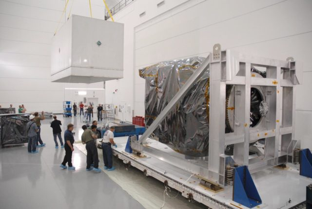 CAPE CANAVERAL, Fla. – At Astrotech Space Operations in Titusville, Fla., the shipping container cover removed from NASA's Solar Dynamics Observatory (right), or SDO, is moved away.  SDO is the first space weather research network mission in NASA's Living With a Star Program.  The spacecraft's long-term measurements will give solar scientists in-depth information about changes in the sun's magnetic field and insight into how they affect Earth.  In preparation for its anticipated November launch, engineers will perform a battery of comprehensive tests to ensure SDO can withstand the stresses and vibrations of the launch itself, as well as what it will encounter in the space environment after launch.  Photo credit: NASA/Tim Jacobs KSC-2009-4017