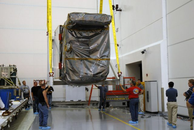 CAPE CANAVERAL, Fla. – At Astrotech Space Operations in Titusville, Fla., workers stand by as a hoist moves NASA's Solar Dynamics Observatory, or SDO, from its transporter.  SDO will be rotated and moved to a work stand. SDO is the first space weather research network mission in NASA's Living With a Star Program.  The spacecraft's long-term measurements will give solar scientists in-depth information about changes in the sun's magnetic field and insight into how they affect Earth.  In preparation for its anticipated November launch, engineers will perform a battery of comprehensive tests to ensure SDO can withstand the stresses and vibrations of the launch itself, as well as what it will encounter in the space environment after launch.   Photo credit: NASA/Cory Huston KSC-2009-4021