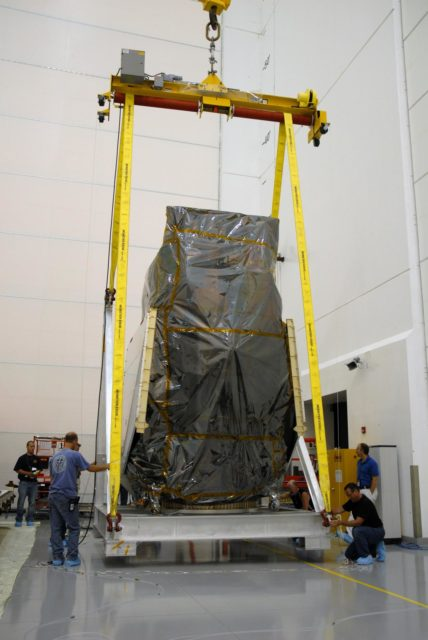 CAPE CANAVERAL, Fla. – At Astrotech Space Operations in Titusville, Fla., workers check the fittings of the hoist supporting NASA's Solar Dynamics Observatory, or SDO, after its rotation.  The SDO will be moved to a work stand. SDO is the first space weather research network mission in NASA's Living With a Star Program.  The spacecraft's long-term measurements will give solar scientists in-depth information about changes in the sun's magnetic field and insight into how they affect Earth.  In preparation for its anticipated November launch, engineers will perform a battery of comprehensive tests to ensure SDO can withstand the stresses and vibrations of the launch itself, as well as what it will encounter in the space environment after launch.   Photo credit: NASA/Cory Huston KSC-2009-4026