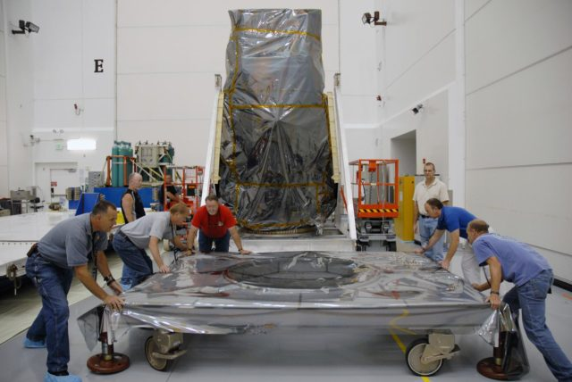 CAPE CANAVERAL, Fla. – At Astrotech Space Operations in Titusville, Fla., workers move a work stand into position to hold NASA's Solar Dynamics Observatory, or SDO, in the background. SDO is the first space weather research network mission in NASA's Living With a Star Program.  The spacecraft's long-term measurements will give solar scientists in-depth information about changes in the sun's magnetic field and insight into how they affect Earth.  In preparation for its anticipated November launch, engineers will perform a battery of comprehensive tests to ensure SDO can withstand the stresses and vibrations of the launch itself, as well as what it will encounter in the space environment after launch.   Photo credit: NASA/Cory Huston KSC-2009-4027
