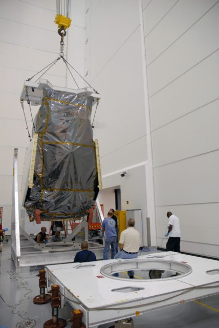 CAPE CANAVERAL, Fla. – At Astrotech Space Operations in Titusville, Fla.,  an overhead cable lifts NASA's Solar Dynamics Observatory, or SDO, to place it on the work stand in the foreground.  SDO is the first space weather research network mission in NASA's Living With a Star Program.  The spacecraft's long-term measurements will give solar scientists in-depth information about changes in the sun's magnetic field and insight into how they affect Earth.  In preparation for its anticipated November launch, engineers will perform a battery of comprehensive tests to ensure SDO can withstand the stresses and vibrations of the launch itself, as well as what it will encounter in the space environment after launch.   Photo credit: NASA/Cory Huston KSC-2009-4028