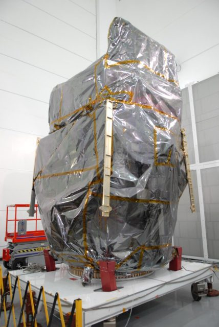 CAPE CANAVERAL, Fla. – At Astrotech Space Operations in Titusville, Fla., NASA's Solar Dynamics Observatory, or SDO, is ready to be unveiled with removal of the protective cover used during shipping.  SDO is the first space weather research network mission in NASA's Living With a Star Program.  The spacecraft's long-term measurements will give solar scientists in-depth information about changes in the sun's magnetic field and insight into how they affect Earth.  In preparation for its anticipated November launch, engineers will perform a battery of comprehensive tests to ensure SDO can withstand the stresses and vibrations of the launch itself, as well as what it will encounter in the space environment after launch.    Photo credit: NASA/Jim Grossmann KSC-2009-4032