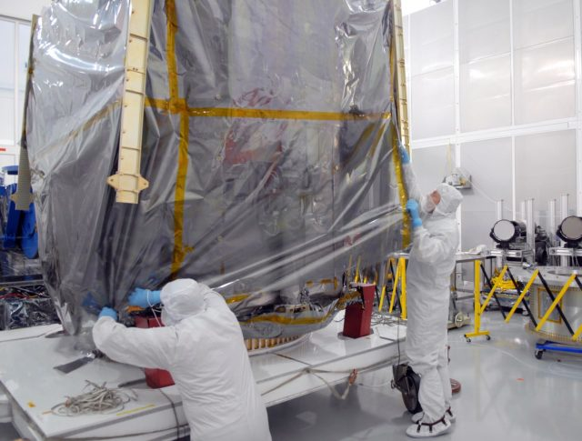 CAPE CANAVERAL, Fla. – At Astrotech Space Operations in Titusville, Fla., technicians begin removing the protective cover around NASA's Solar Dynamics Observatory, or SDO. SDO is the first space weather research network mission in NASA's Living With a Star Program.  The spacecraft's long-term measurements will give solar scientists in-depth information about changes in the sun's magnetic field and insight into how they affect Earth.  In preparation for its anticipated November launch, engineers will perform a battery of comprehensive tests to ensure SDO can withstand the stresses and vibrations of the launch itself, as well as what it will encounter in the space environment after launch.    Photo credit: NASA/Jim Grossmann KSC-2009-4033