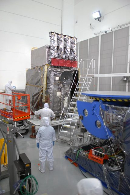 CAPE CANAVERAL, Fla. – At Astrotech Space Operations in Titusville, Fla., technicians remove portions of the protective cover wrapped around NASA's Solar Dynamics Observatory, or SDO. SDO is the first space weather research network mission in NASA's Living With a Star Program.  The spacecraft's long-term measurements will give solar scientists in-depth information about changes in the sun's magnetic field and insight into how they affect Earth.  In preparation for its anticipated November launch, engineers will perform a battery of comprehensive tests to ensure SDO can withstand the stresses and vibrations of the launch itself, as well as what it will encounter in the space environment after launch.    Photo credit: NASA/Jim Grossmann KSC-2009-4036