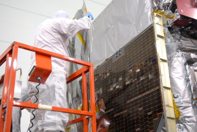 CAPE CANAVERAL, Fla. – At Astrotech Space Operations in Titusville, Fla., a technician removes part of the protective cover from the solar panel on NASA's Solar Dynamics Observatory, or SDO. SDO is the first space weather research network mission in NASA's Living With a Star Program.  The spacecraft's long-term measurements will give solar scientists in-depth information about changes in the sun's magnetic field and insight into how they affect Earth.  In preparation for its anticipated November launch, engineers will perform a battery of comprehensive tests to ensure SDO can withstand the stresses and vibrations of the launch itself, as well as what it will encounter in the space environment after launch.    Photo credit: NASA/Jim Grossmann KSC-2009-4037