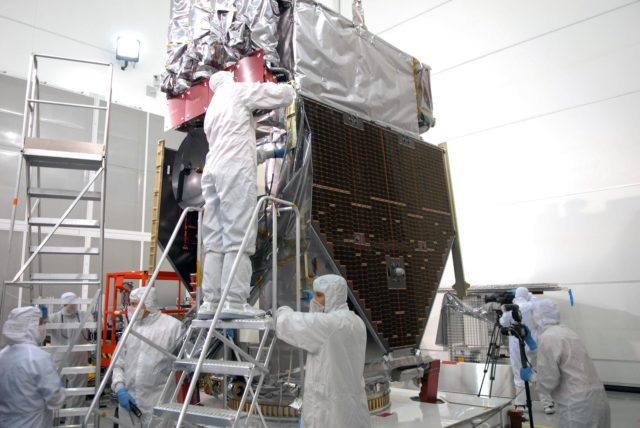 CAPE CANAVERAL, Fla. – At Astrotech Space Operations in Titusville, Fla., technicians remove the final portions of the protective cover wrapped around NASA's Solar Dynamics Observatory, or SDO. SDO is the first space weather research network mission in NASA's Living With a Star Program.  The spacecraft's long-term measurements will give solar scientists in-depth information about changes in the sun's magnetic field and insight into how they affect Earth.  In preparation for its anticipated November launch, engineers will perform a battery of comprehensive tests to ensure SDO can withstand the stresses and vibrations of the launch itself, as well as what it will encounter in the space environment after launch.    Photo credit: NASA/Jim Grossmann KSC-2009-4040