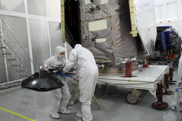 CAPE CANAVERAL, Fla. – Engineers at Astrotech Space Operations in Titusville, Fla.,  lower the high-gain antenna on the Solar Dynamics Observatory to gain access to the battery compartment for installation of the flight battery. SDO is the first space weather research network mission in NASA's Living With a Star Program.  The spacecraft's long-term measurements will give solar scientists in-depth information about changes in the sun's magnetic field and insight into how they affect Earth.  In preparation for its anticipated November launch, engineers will perform a battery of comprehensive tests to ensure SDO can withstand the stresses and vibrations of the launch itself, as well as what it will encounter in the space environment after launch.     Photo credit: NASA/Jack Pfaller KSC-2009-4065