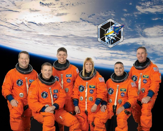 JOHNSON SPACE CENTER, Houston - STS130-S-002 - Attired in training versions of their shuttle launch and entry suits, these six astronauts take a break from training to pose for the STS-130 crew portrait. Seated are astronauts George Zamka (right), commander; and Terry Virts, pilot. From the left (standing) are astronaut Nicholas Patrick, Robert Behnken, Kathryn Hire and Stephen Robinson, all mission specialists. KSC-2009-6950