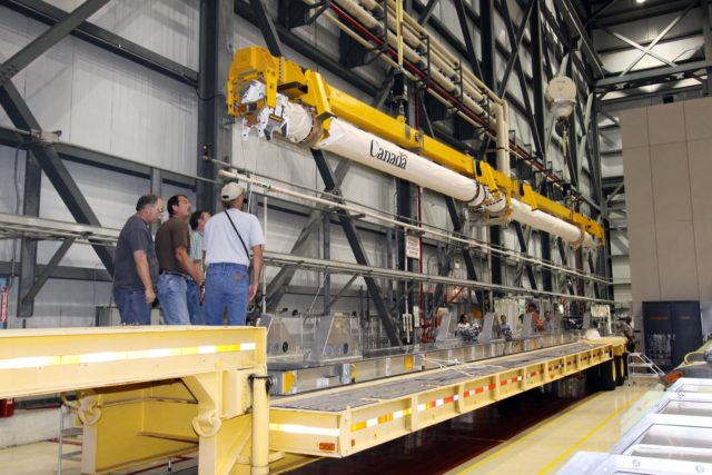 CAPE CANAVERAL, Fla. –In NASA Kennedy Space Center's Orbiter Processing Facility bay 2, a crane lowers space shuttle Endeavour's Orbiter Boom Sensor System toward a mobile stand.  The OBSS was removed from Endeavour's payload bay.  After returning from the STS-127 mission July 31, 2009, Endeavour now is being processed for the STS-130 mission targeted for Feb. 4, 2010.  Endeavour will deliver to the International Space Station the Tranquility pressurized module that will provide room for many of the station's life support systems.   Photo credit: NASA/Jack Pfaller KSC-2009-4977
