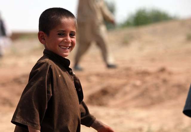 A local Afghan child greets Marines