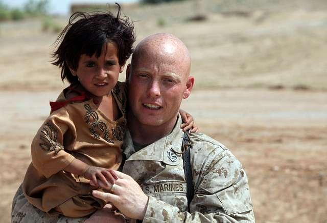 A Marine embraces an Afghan child