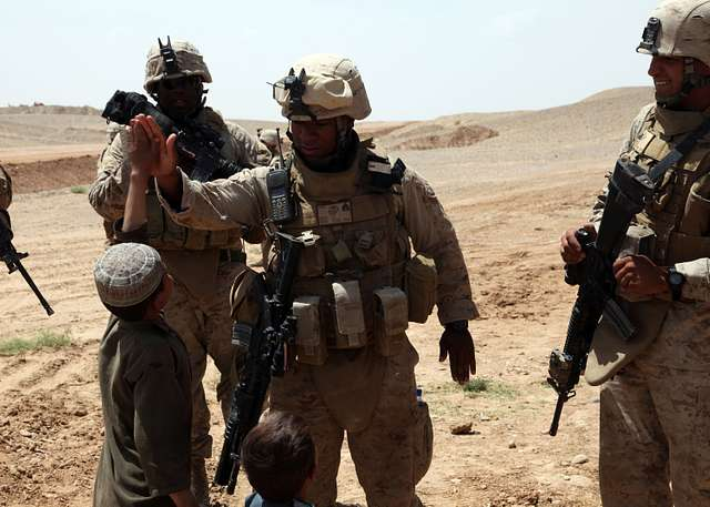 Marines high-five with an Afghan child