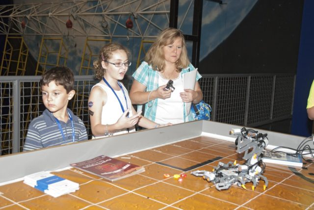 "CAPE CANAVERAL, Fla. -- At the Astronaut Hall of Fame near the Kennedy Space Center Visitor Complex in Florida, fifth- through eighth-grade students and their parents participate in a Lego robotics demonstration during the last NASA family education night event. Other activities included ""gee-whiz"" presentations, astronaut appearances, a hovercraft, vortex cannon and alternative fuel vehicles, which promote science, technology, engineering and mathematics (STEM) education.    The event is part of NASA's Summer of Innovation initiative to provide interactive learning experiences to middle school students nationwide during the summer months. The program is a cornerstone of the Educate to Innovate campaign announced by President Barack Obama in November 2009. Photo credit: NASA/Charisse Nahser KSC-2010-4523"