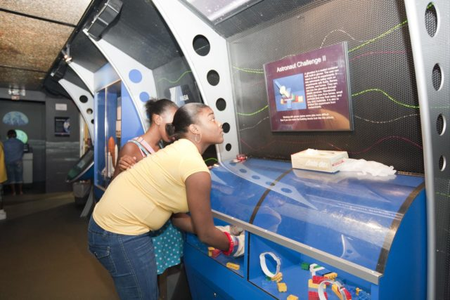 """ORLANDO, Fla. -- Attendees of the 2010 Tom Joyner Family Reunion use astronaut gloves to perform a task at the Gaylord Palms Convention Center in Orlando, Fla. To encourage student attendees to focus on pursuing careers in science, technology, engineering and mathematics (STEM), NASA featured some of its greatest legends and trailblazers during a panel discussion at the reunion event.    NASA's Education Office sponsored the panel discussion and educational activities as part of the agency's """"Summer of Innovation"""" initiative and the federal """"Educate to Innovate"""" campaign. Photo credit: NASA/Amanda Diller KSC-2010-4569"""