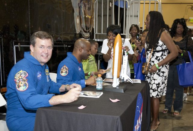 """ORLANDO, Fla. -- Attendees of the 2010 Tom Joyner Family Reunion stand in line to receive an autograph from NASA astronauts Mike Foreman, left, and Leland Melvin at the Gaylord Palms Convention Center in Orlando, Fla. To encourage student attendees to focus on pursuing careers in science, technology, engineering and mathematics (STEM), NASA featured some of its greatest legends and trailblazers during a panel discussion at the reunion event. Foreman and Melvin are both veterans of two space shuttle missions.    NASA's Education Office sponsored the panel discussion and educational activities as part of the agency's """"Summer of Innovation"""" initiative and the federal """"Educate to Innovate"""" campaign. Photo credit: NASA/Amanda Diller KSC-2010-4573"""