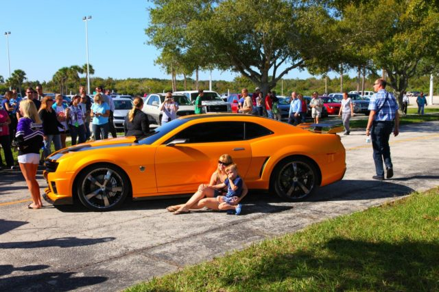 "CAPE CANAVERAL, Fla. -- NASA Kennedy Space Center employees in Florida were provided a unique photo opportunity on Oct. 8 from some of the robot 'stars' of the upcoming movie, ""Transformers 3."" Paramount Pictures filmed scenes for the movie at Kennedy from Oct. 4 through 8. As a show of appreciation for sharing the space center with the ""Transformers 3"" cast and crew, Kennedy employees and their families were invited to see two Transformers characters, Optimus Prime and Bumblebee, in their vehicle form, on display outside Kennedy Space Center Visitor Complex. In this image Kennedy employee family members pose for a photo in front of 'Bumblebee.' ""Transformers 3"" is due out in theaters summer 2011. Photo credit: NASA/Frank Michaux KSC-2010-5029"