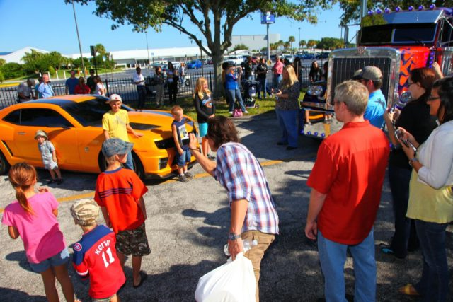 "CAPE CANAVERAL, Fla. -- NASA Kennedy Space Center employees in Florida were provided a unique photo opportunity on Oct. 8 from some of the robot 'stars' of the upcoming movie, ""Transformers 3."" Paramount Pictures filmed scenes for the movie at Kennedy from Oct. 4 through 8. As a show of appreciation for sharing the space center with the ""Transformers 3"" cast and crew, Kennedy employees and their families were invited to see two Transformers characters, Optimus Prime and Bumblebee, in their vehicle form, on display outside Kennedy Space Center Visitor Complex. In this image Kennedy employee family members pose for a photo in front of 'Bumblebee,' while 'Optimus Prime' is on display to its right. ""Transformers 3"" is due out in theaters summer 2011. Photo credit: NASA/Frank Michaux KSC-2010-5030"