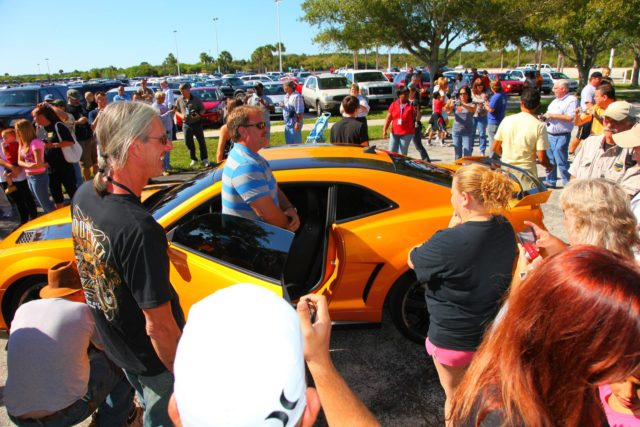 "CAPE CANAVERAL, Fla. -- NASA Kennedy Space Center employees in Florida were provided a unique photo opportunity on Oct. 8 from some of the robot 'stars' of the upcoming movie, ""Transformers 3."" Paramount Pictures filmed scenes for the movie at Kennedy from Oct. 4 through 8. As a show of appreciation for sharing the space center with the ""Transformers 3"" cast and crew, Kennedy employees and their families were invited to see two Transformers characters, Optimus Prime and Bumblebee, in their vehicle form, on display outside Kennedy Space Center Visitor Complex. In this image Kennedy employee family members are enjoying the opportunity to gather around 'Bumblebee.' ""Transformers 3"" is due out in theaters summer 2011. Photo credit: NASA/Frank Michaux KSC-2010-5032"