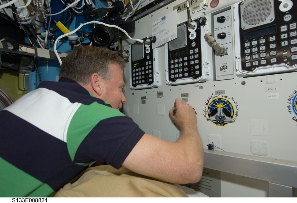 S133-E-008824 (5 March 2011) --- NASA astronaut Steve Lindsey, STS-133 commander, signs the STS-133 patch, which was added to the growing collection of insignias representing crews who performed spacewalks from the Quest airlock of the International Space Station. Photo credit: NASA or National Aeronautics and Space Administration s133e008824