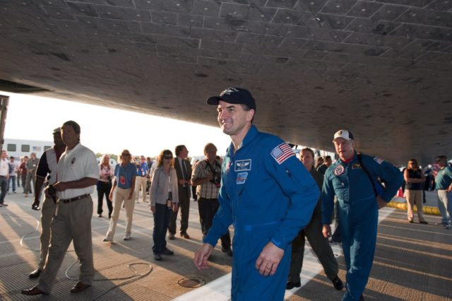 CAPE CANAVERAL, Fla. -- The STS-135 Mission Specialist Rex Walheim, front center, takes a stroll underneath space shuttle Atlantis following a successful mission to the International Space Station. Four astronauts brought Atlantis home to the Shuttle Landing Facility's Runway 15 at NASA's Kennedy Space Center in Florida at 5:57 a.m. EDT bringing a close NASA's Space Shuttle Program. Atlantis' final return from space completed a 13-day, 5.2-million-mile journey to the International Space Station.                  STS-135 delivered spare parts, equipment and supplies in the Raffaello multi-purpose logistics module that will sustain station operations for the next year. STS-135 was the 33rd and final flight for Atlantis, which has spent 307 days in space, orbited Earth 4,848 times and traveled 125,935,769 miles. For more information visit, www.nasa.gov/mission_pages/shuttle/shuttlemissions/sts135/index.html. Photo credit: NASA/Kim Shiflett KSC-2011-5682