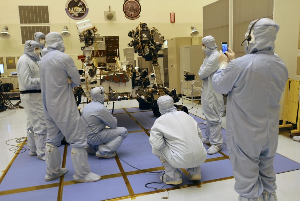 CAPE CANAVERAL, Fla. -- Under the watchful eyes of the spacecraft technicians in the Payload Hazardous Servicing Facility at NASA's Kennedy Space Center in Florida, the robotic arm of the Mars Science Laboratory (MSL) rover, Curiosity, moves into place against the body of the spacecraft.    The arm will hold and maneuver instruments that will help scientists analyze Martian rocks and soil. Much like a human arm, the robotic arm has flexibility through shoulder, elbow, and wrist joints that permit the arm to extend, bend, and angle precisely against rocks and soil to grind away layers, take microscopic images and analyze their elemental composition.  At the end of the arm is a hand-like structure, the turret, for holding various tools that can spin through a 350-degree turning range.      A United Launch Alliance Atlas V-541 configuration will be used to loft MSL into space. Curiosity's 10 science instruments are designed to search for evidence on whether Mars has had environments favorable to microbial life, including chemical ingredients for life.  The unique rover will use a laser to look inside rocks and release its gasses so that the rover's spectrometer can analyze and send the data back to Earth. MSL is scheduled to launch Nov. 25 from Space Launch Complex 41 on Cape Canaveral Air Force Station in Florida. For more information, visit http://www.nasa.gov/msl. Photo credit: NASA/Charisse Nahser KSC-2011-6473