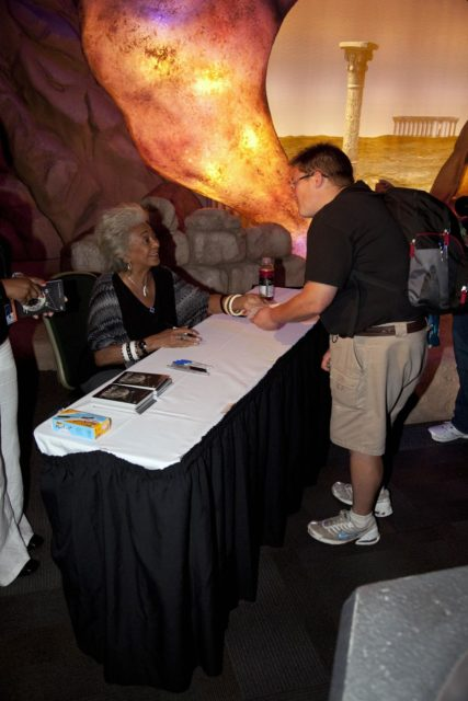 """CAPE CANAVERAL, Fla. – Actress Nichelle Nichols (Lt. Uhura on Star Trek) signs autographs for a guest at the Kennedy Space Center Visitor Complex in Florida during activities for the agency's Gravity Recovery and Interior Laboratory mission (GRAIL). Nichols was on hand to celebrate the 45th anniversary of the first airing of the Star Trek television series. The Kennedy Space Center Visitor Complex is hosting """"Star Trek: The Exhibition"""" to show visitors where """"science fiction meets science fact.""""    GRAIL will fly twin spacecraft in tandem around the moon to precisely measure and map variations in the moon's gravitational field. The mission will provide the most accurate global gravity field to date for any planet, including Earth. This detailed information will reveal differences in the density of the moon's crust and mantle and will help answer fundamental questions about the moon's internal structure, thermal evolution, and history of collisions with asteroids. The aim is to map the moon's gravity field so completely that future moon vehicles can safely navigate anywhere on the moon's surface. For more information, visit http://www.nasa.gov/grail. Photo credit: NASA/Frankie Martin KSC-2011-6853"""