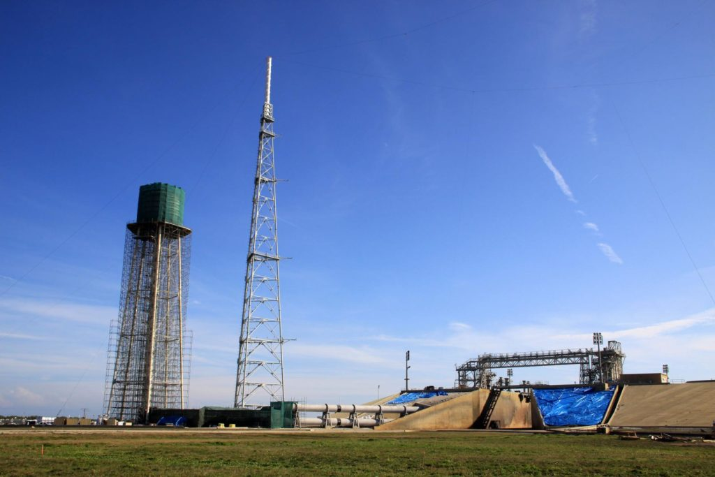 CAPE CANAVERAL, Fla. - At NASA's Kennedy Space Center in Florida, preparations are underway to sandblast and paint the 290-foot-high water tower at Launch Pad 39B. Scaffolding surrounds the tower and a special covering has been placed around the tank.    The water towers at Launch Complex 39, which includes pad A and B, were part of the sound suppression system used during space shuttle launches. Water stored in the 300,000-gallon tank would be released just prior to main engine ignition and flow by gravity to special mobile launcher platform (MLP) outlets. Nine seconds after shuttle liftoff, the peak flow rate was 900,000 gallons per minute and helped to protect the orbiter and payloads from being damaged by acoustical energy reflected from the MLP during liftoff. Photo Credit: NASA/Jim Grossmann KSC-2012-1296