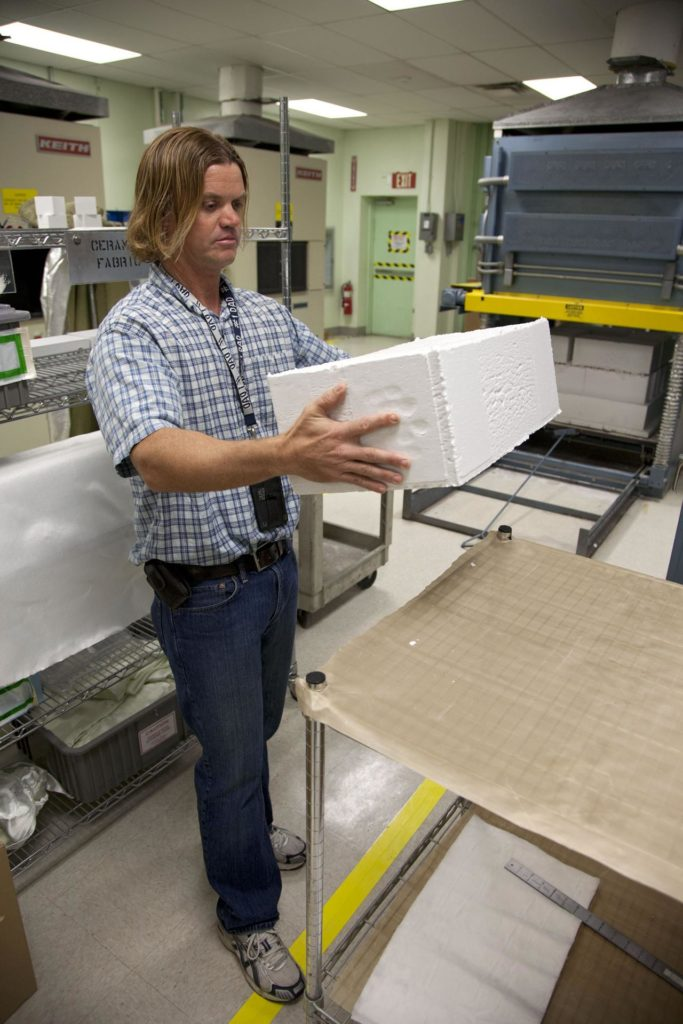 Tim Wright, a United Space Alliance engineering manager at NASA's Kennedy Space Center in Florida, unpacks the heat shield tiles that will be installed to the backshell of the Orion Multi-Purpose Crew Vehicle's Exploration Flight Test EFT-1 capsule. The tiles are being manufactured and inspected in Kennedy's Thermal Protection System Facility. The tiles will be baked at 2,200 degrees F to cure their ceramic coating. EFT-1 will be used during Orion's first test flight in space. For more information, visit www.nasa.gov/orion. Photo credit: Frankie Martin KSC-2012-1572