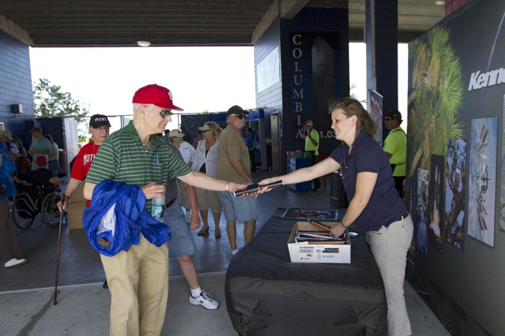VIERA, Fla. – Tiffany Lindsley, with Education and External Relations at NASA's Kennedy Space Center in Florida, hands out information on some of the contributions the space agency has made to sports, transportation and everyday life to a baseball fan attending Space Day at the Space Coast Stadium.  Bob Cabana, director of Kennedy, was on hand to throw the first pitch of a spring training game between Major League Baseball's Washington Nationals and the Houston Astros. A full-scale test version of NASA's new Orion Multi-Purpose Crew Vehicle was on display outside the stadium for the occasion to show the public the spacecraft under development that will take astronauts farther into space than ever before.    For more information, visit http://www.nasa.gov/kennedy.  Photo credit: NASA/Kim Shiflett KSC-2012-1685