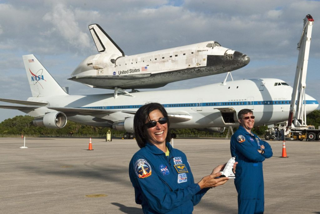 CAPE CANAVERAL, Fla. – At the Shuttle Landing Facility at NASA's Kennedy Space Center in Florida, STS-133 Mission Specialists Nicole Stott and Michael Barratt pose for a photographer in front of a Shuttle Carrier Aircraft on which space shuttle Discovery has been secured for departure.  Stott and Barratt were members of the crew to fly on Discovery's final mission in February and March 2011.  Other members of the STS-133 crew were Commander Steve Lindsey, Pilot Eric Boe, and Mission Specialists Alvin Drew and Steve Bowen. Discovery is scheduled to depart from Kennedy for the final time tomorrow morning.    Also known as an SCA, the aircraft is a Boeing 747 jet, originally manufactured for commercial use, which was modified by NASA to transport the shuttles between destinations on Earth. The SCA designated NASA 905 is assigned to the remaining ferry missions, delivering the shuttles to their permanent public display sites.  NASA 905 is scheduled to ferry Discovery to the Washington Dulles International Airport in Virginia on April 17, after which the shuttle will be placed on display in the Smithsonian's National Air and Space Museum Steven F. Udvar-Hazy Center. For more information on the SCA, visit http://www.nasa.gov/centers/dryden/news/FactSheets/FS-013-DFRC.html. For more information on shuttle transition and retirement activities, visit http://www.nasa.gov/transition. Photo credit: NASA/Tim Jacobs KSC-2012-2296