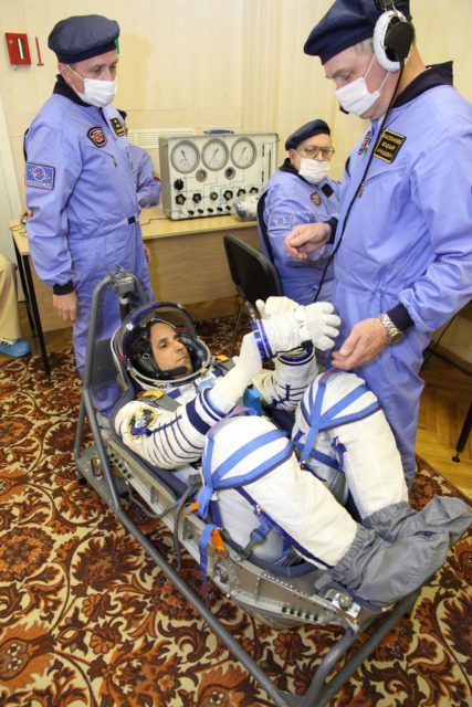 "At the Baikonur Cosmodrome in Kazakhstan, Expedition 31/32 Flight Engineer Joe Acaba of NASA conducts pressure and leak checks to his ""Sokol"" launch and entry suit May 3, 2012 during a suited dress rehearsal of launch day activities as part of the final training he, Soyuz Commander Gennady Padalka and Flight Engineer Sergei Revin are undergoing in advance of their launch May 15 on the Soyuz TMA-04M spacecraft to the International Space Station.  NASA/Victor Zelentsov jsc2012e049719"