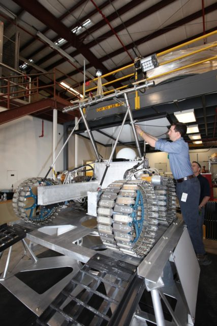 CAPE CANAVERAL, Fla. – Nick Cristello, an engineer with Neptec, a contractor to the Canadian Space Agency, attaches navigation-related wiring on the prototype rover Artemis Jr. in a test facility behind the Operations and Checkout Building at NASA's Kennedy Space Center in Florida before conducting a dry run.  The rover is one component of NASA's Regolith and Environment Science and Oxygen and Lunar Volatile Extraction, or RESOLVE, project and is positioned atop RESOLVE's prototype lander.       RESOLVE consists of a rover and drill provided by the Canadian Space Agency to support a NASA payload that is designed to prospect for water, ice and other lunar resources. RESOLVE also will demonstrate how future explorers can take advantage of resources at potential landing sites by manufacturing oxygen from soil. NASA will conduct field tests in July outside of Hilo, Hawaii, with equipment and concept vehicles that demonstrate how explorers might prospect for resources and make their own oxygen for survival while on other planetary bodies.  For more information, visit http://www.nasa.gov/exploration/analogs/index.html.  Photo credit: NASA/Dimitri Gerondidakis KSC-2012-3273