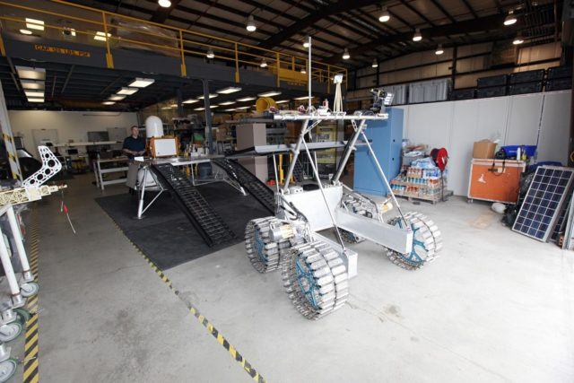 CAPE CANAVERAL, Fla. – In a test facility behind the Operations and Checkout Building at NASA's Kennedy Space Center in Florida, the prototype rover Artemis Jr. for NASA's Regolith and Environment Science and Oxygen and Lunar Volatile Extraction, or RESOLVE, project has dismounted the RESOLVE lander during a dry run using the ramps attached to the prototype lander.    RESOLVE consists of a rover and drill provided by the Canadian Space Agency to support a NASA payload that is designed to prospect for water, ice and other lunar resources. RESOLVE also will demonstrate how future explorers can take advantage of resources at potential landing sites by manufacturing oxygen from soil. NASA will conduct field tests in July outside of Hilo, Hawaii, with equipment and concept vehicles that demonstrate how explorers might prospect for resources and make their own oxygen for survival while on other planetary bodies.  For more information, visit http://www.nasa.gov/exploration/analogs/index.html.  Photo credit: NASA/Dimitri Gerondidakis KSC-2012-3276