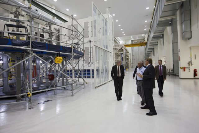 CAPE CANAVERAL, Fla. – Charles Bolden, NASA administrator, center, is shown the high bay at the Operations and Checkout Building at NASA's Kennedy Space Center in Florida by NASA's Scott Wilson, left, and Lockheed Martin's Jules Schneider, foreground. Lockheed Martin is processing an Orion spacecraft that will make an uncrewed flight test in 2014. Photo credit: NASA/Kim Shifflett KSC-2012-4244